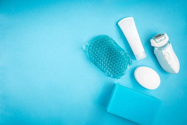 Mesa feminina de banho azul. sabonete, esponja, massagista, creme e depilador. produtos de banho. limpeza e cuidados com a pele.