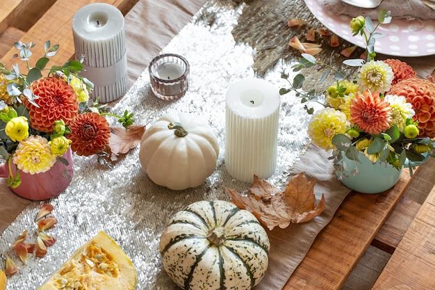 Mesa festiva com velas de abóboras e flores de crisântemo