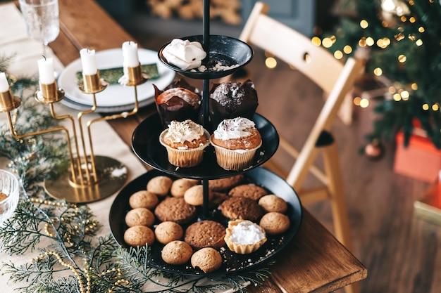 Mesa festiva de natal com biscoitos doces e bolos na cozinha com enfeites.
