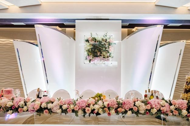 Mesa festiva de recém-casados decorados com composição de flores e folhagens no salão de banquetes do casamento. festa de casamento na tenda.
