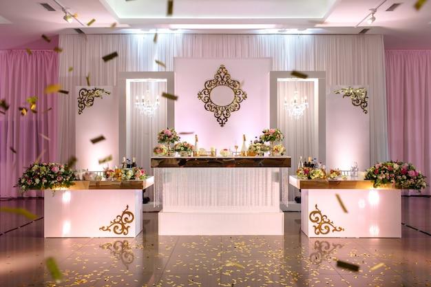Mesa festiva decorada com composição de flores brancas, vermelhas e rosa e vegetação no salão de banquetes.