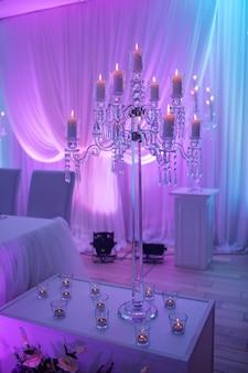 Mesa festiva decorada com composição de velas e castiçais de prata em luz colorida no salão de banquetes. apresente recém-casados na área do banquete na festa de casamento.