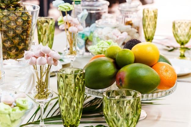 Mesa festiva, decorada com vasos, frutas e doces.