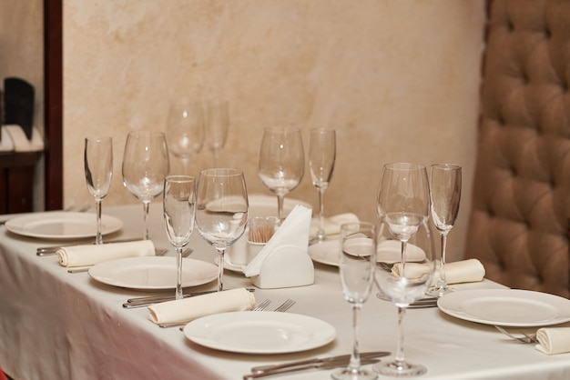 Mesa festiva lindamente decorada com pratos e copos em um restaurante