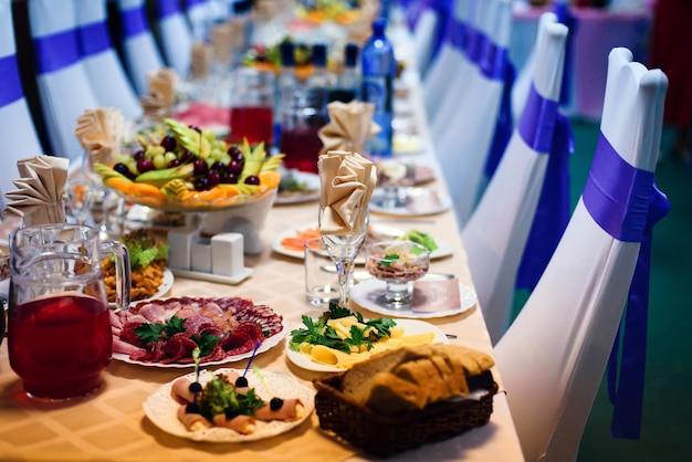 Mesa festiva no restaurante com pratos, copos e talheres em uma toalha de mesa branca