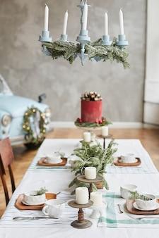 Mesa festiva servida para o brunch de natal com lindos pratos festivos, taças, candelabros com velas e ramos de pinheiro. véspera de natal.