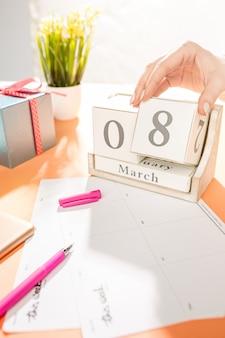 Mesa laranja com xícara de telefone, presente, flores e caderno
