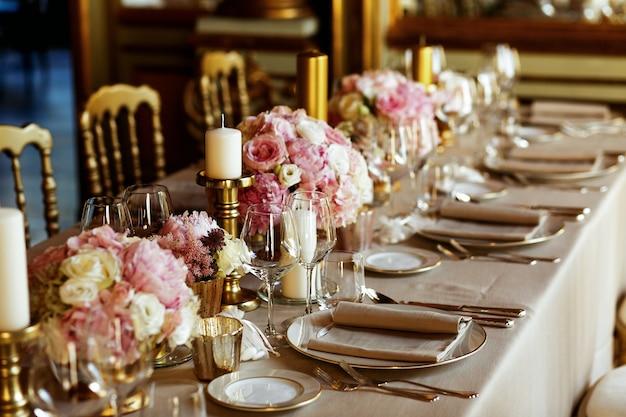 Mesa longa servida com louça de porcelana e talheres brilhantes servidos com flores de cor-de-rosa
