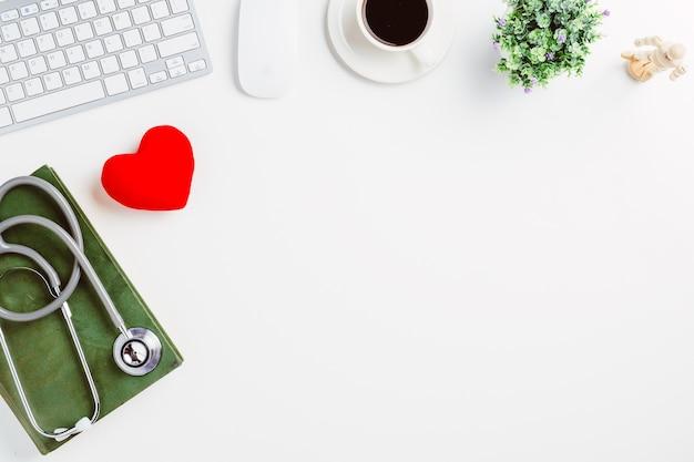 Mesa médica com estetoscópio, livro, coração, laptop, mouse e xícara de café na mesa branca.
