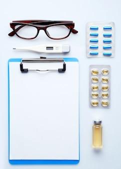 Mesa médica com remédios e óculos, vista de cima