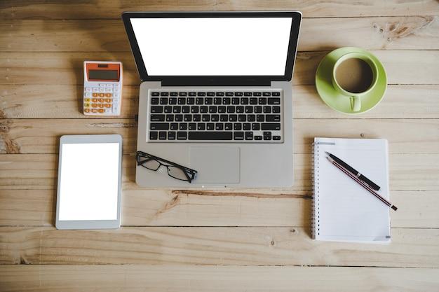 Mesa mesa de madeira com calculadora e tablet, xícara de café, lápis-lápis no notebook