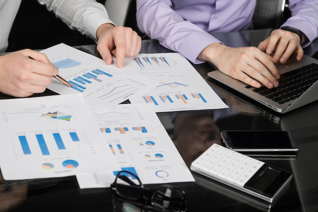 Mesa no escritório com gráficos, um laptop e mãos masculinas