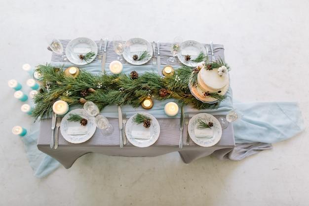 Mesa para convidados, decorada com velas, servida com talheres e louça e coberta com uma toalha de mesa