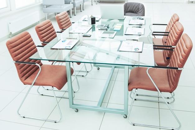 Mesa para negociações com os gráficos financeiros preparados e equipamentos de escritório na sala de conferências