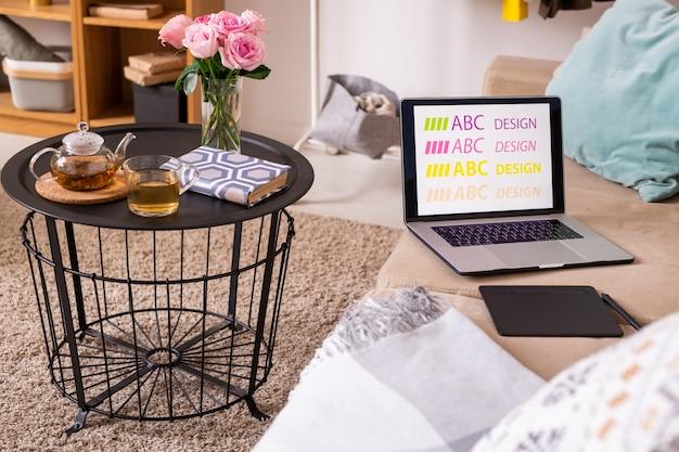 Mesa pequena com livro, chá verde e rosas cor de rosa em cima do tapete macio ao lado do sofá confortável com bloco, caneta e laptop do designer