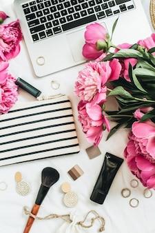 Mesa plana, vista de cima, moda feminina, mesa de escritório com flores de peônia, laptop, cosméticos, acessórios na superfície branca