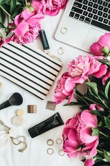 Mesa plana, vista superior, moda feminina escritório com flores peônia, laptop, cosméticos, acessórios na superfície branca