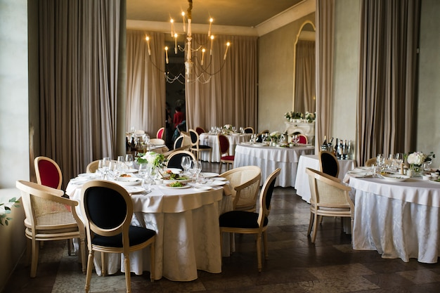 Mesa posta no banquete de casamento no restaurante, estilo clássico com toalhas de mesa e guardanapos brancos, vasos com flores.