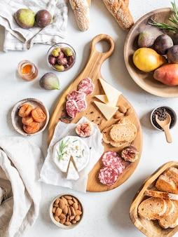 Mesa posta para lanches. variedade de queijo, azeitonas, salsichas, fatias de baguete, figos, nozes na placa de madeira, postura plana. vista do topo.