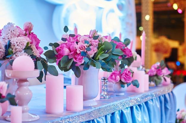 Mesa posta para recepção de casamento com velas e buquês de flores