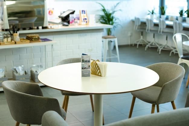 Mesa redonda branca com folheto e guardanapos de papel cercada por um grupo de poltronas confortáveis em um café aconchegante