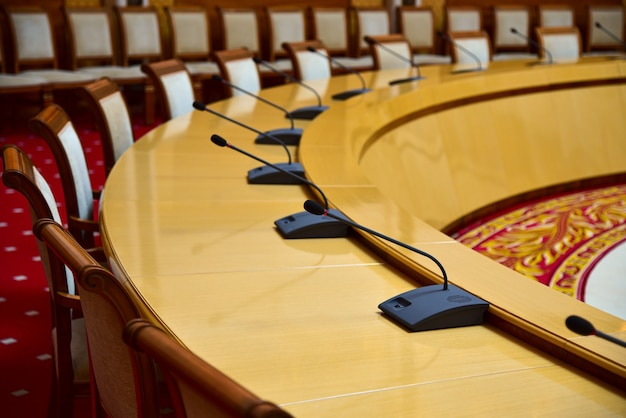 Mesa redonda com microfones para negociações diplomáticas no salão