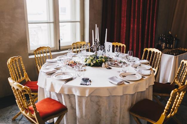 Mesa redonda com muitas cadeiras servidas por muitas pessoas em estilo retro com toalha de mesa branca