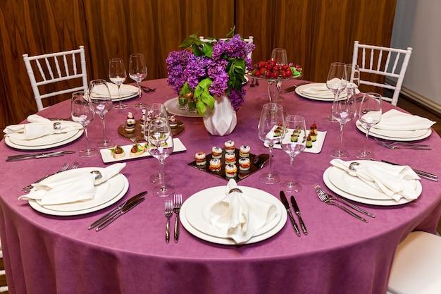 Mesa redonda com toalha rosa e talheres com petiscos para o banquete. catering, mesas de servidor para bonquet