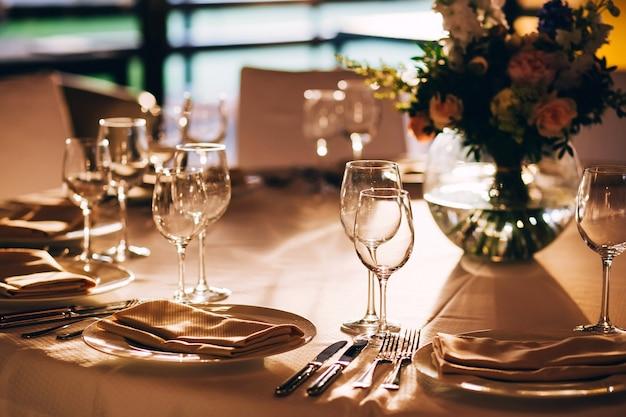 Mesa redonda com uma toalha de mesa branca. a mesa está decorada com um vaso de flores. copo de vinho e taça de champanhe.