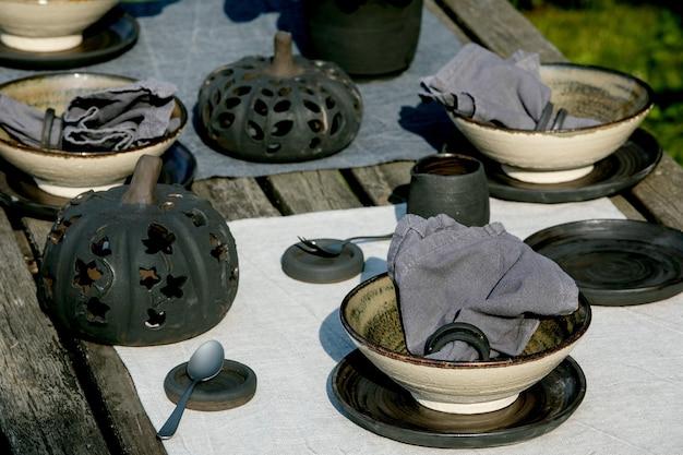 Mesa rústica ao ar livre em jardim com talheres de cerâmica artesanais vazios