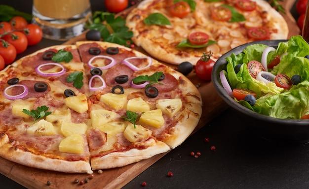 Mesa rústica de pedra escura com vários tipos de pizza italiana, vista de cima. almoço fast food, comemoração