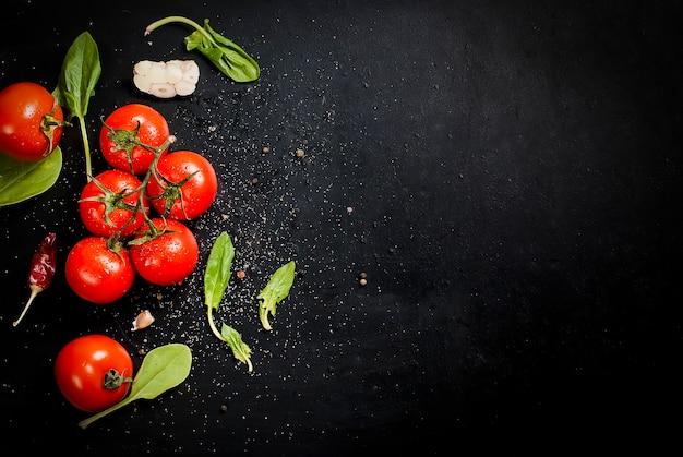 Mesa rústica preta com ramo de tomate e ervas, vista superior