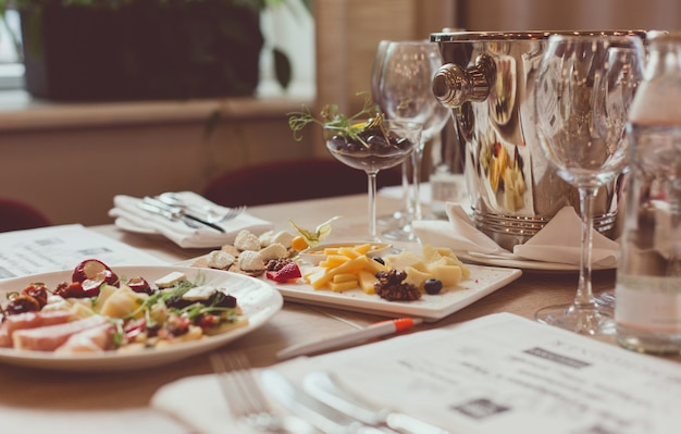 Mesa servida com aperitivos, talheres, copos e escarradeira para degustação de vinhos.