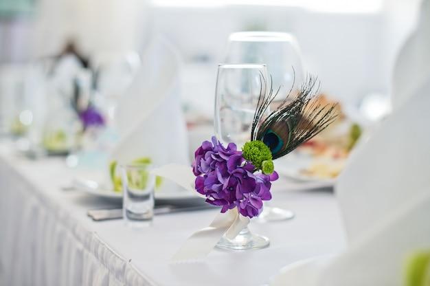 Mesa servida com pratos, guardanapos brancos e copos decorados com flores roxas, jantar no restaurante