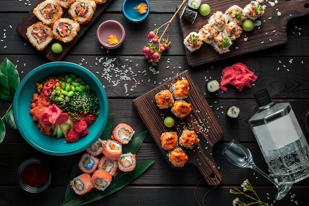 Mesa servida com sushi, rolos e comida japonesa tradicional em fundo escuro. vista do topo.