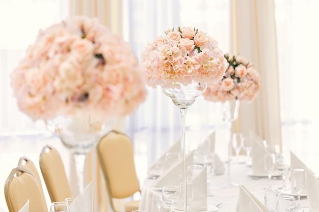 Mesa servida para jantar de evento com talheres e copos, decorada com composições florais em vasos.