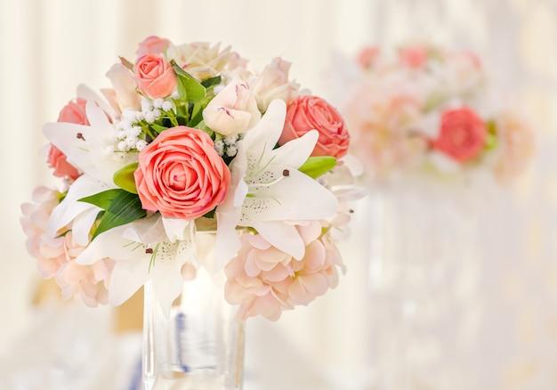 Mesa servida para jantar de evento, decorada com composições florais em vasos em tons rosa e coral.