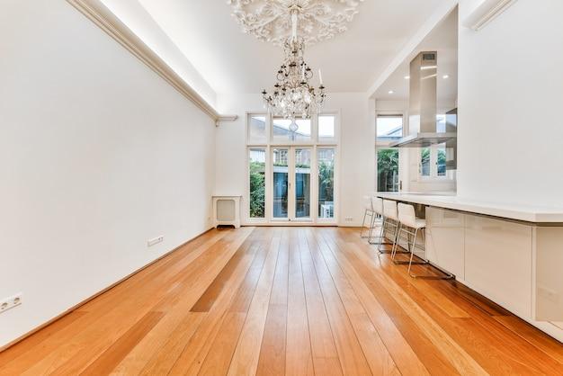 Mesa simples com cadeiras localizadas sob um lustre elegante perto da lareira e portas na sala de jantar elegante