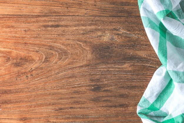 Mesa vazia coberta com toalha de mesa sobre fundo de parede de cimento marrom,