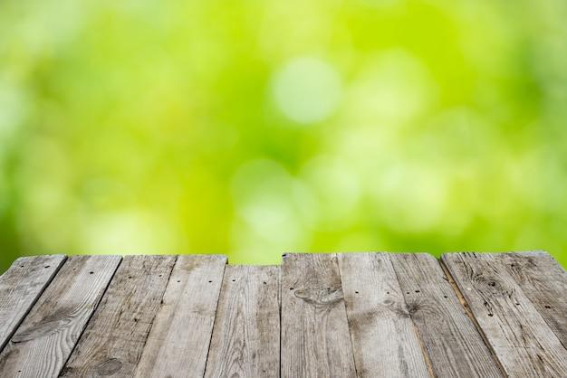 Mesa vazia de deck de madeira com bokeh de folhagem