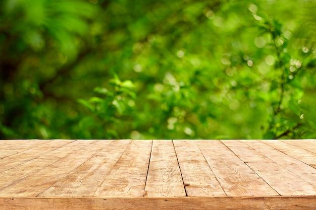 Mesa vazia de deck de madeira com fundo de folhagem bokeh.