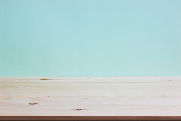 Mesa vazia de deck de madeira sobre fundo de papel de parede de hortelã