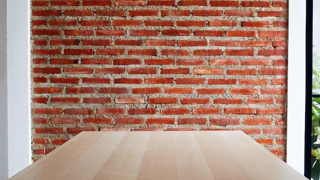 Mesa vazia de tábua de madeira com fundo de parede de tijolos vermelhos