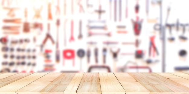 Mesa vazia de tábua de madeira marrom claro na frente com ferramentas de layout blurrry do técnico na tábua de madeira branca