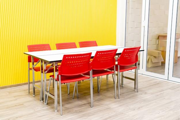Mesa vazia e cadeira vermelha no quarto