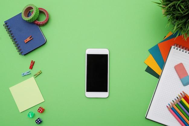 Mesa verde com artigos de papelaria e smartphone, vista superior