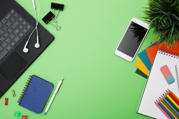 Mesa verde com artigos de papelaria, vista superior, copypace