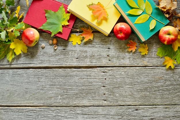 Mesa vintage de outono com maçãs, folhas caídas, livros antigos sobre fundo de mesa de madeira velha