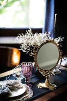 Mesa vintage retrô. arranjo na mesa, espelho antigo, pratos, caneca vintage. espelho antigo na mesa