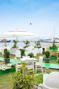 Mesas de café servidas com uma toalha de mesa branca perto da costa do mar para umas férias relaxantes